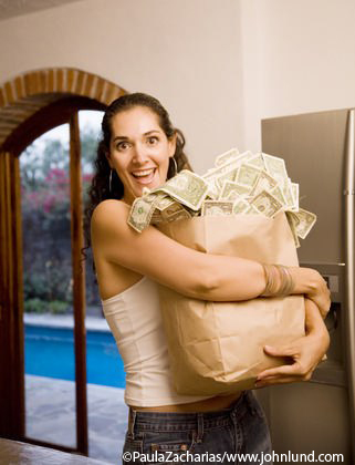Stock photo of a happy smiling hispanic woman with her arms wrapped around a grocery bag stuffed full of money. Bills are overflowing the top and spilling out. Gobs of money and a bag of  cash.